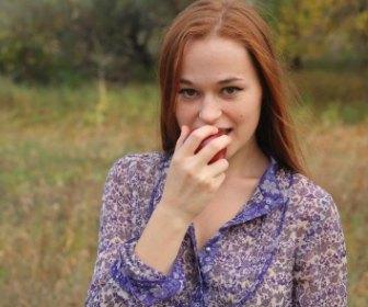 リンゴをかじる女性。