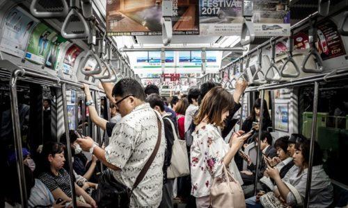 電車の中でスマホを見る人