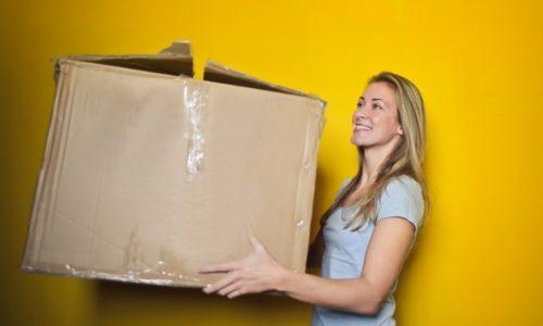 ダンボール箱を持つ女性。