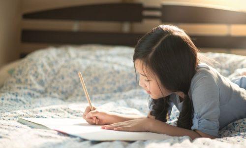 ベッドの上でものを書く女性