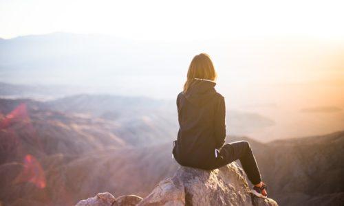 岩山い座る女性の後ろ姿