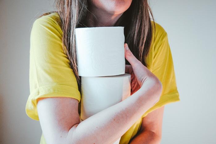 トイレットペーパーを抱える女性