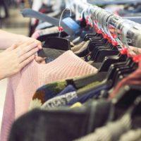店でセーターを選ぶ人