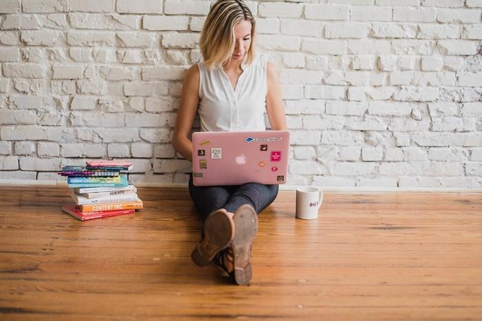 床に座ってパソコンする女性