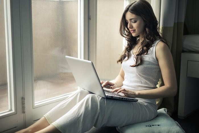 窓際でノートパソコンに向かう若い女性