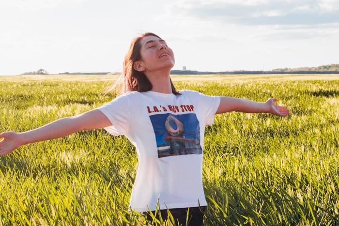 野原で両手を広げて立つ女性