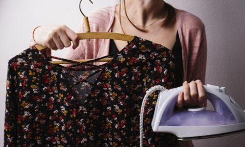 服とアイロンを持つ女性