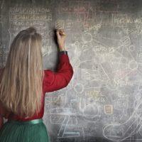 黒板に図を描いている女性