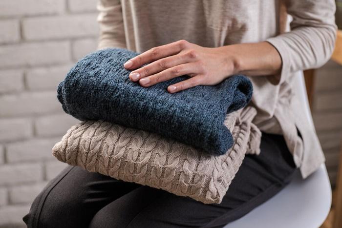 セーターを持つ女性