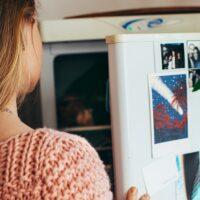 冷蔵庫の扉を開ける若い女性