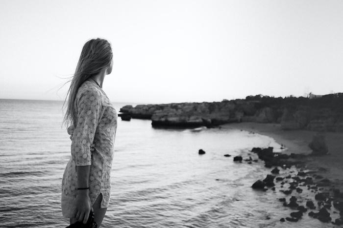 海辺で後悔している若い女性