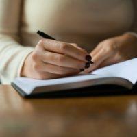 ノートに何か書いている人