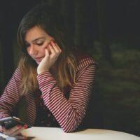 スマホを見ながら考え事をしている女性