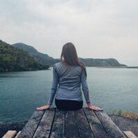 湖を見てリラックスする女性