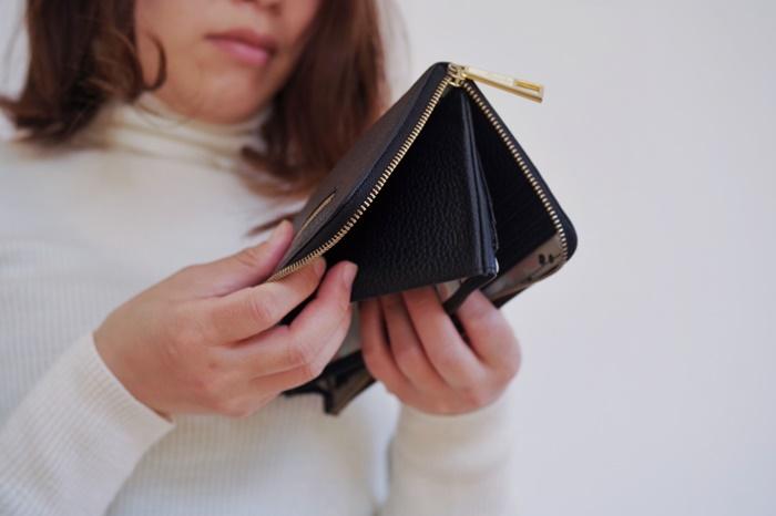 財布をひっくり返す女性
