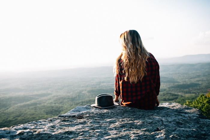 岩の上に座っている若い女性