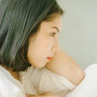 考え事をしている若い女性