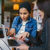 パソコンを見ながら話をしている女性2人
