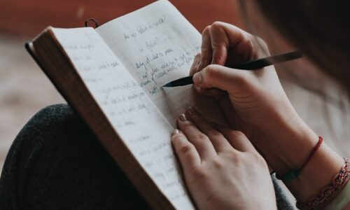 手帳に何か書いている人'